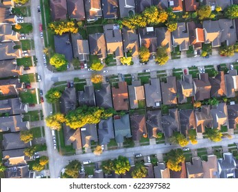 Aerial view of residential houses and driveways neighborhood during a fall sunset. Tightly packed homes, surrounds with green tree flyover in Houston, Texas, US. Suburban housing community development