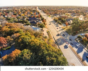 Aerial view residential houses near highway with traffic near Dallas, Texas, USA. Horizontal view of upscale neighborhood with colorful autumn leaves in Flower Mound