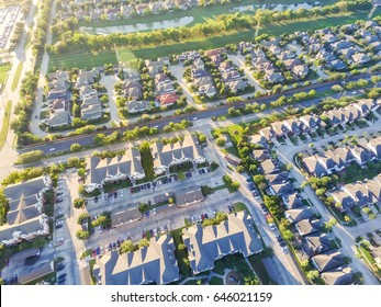 Aerial view of residential houses neighborhood and apartment building complex at sunset. Tightly packed homes, driveway surrounds green tree flyover in Houston, Texas, US. Suburban housing development