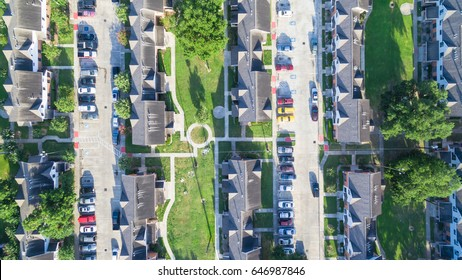 Aerial view of residential houses neighborhood in suburban area of downtown Houston, Texas, US. Tightly packed homes, driveway surrounded with green tree flyover in early morning. Housing development.