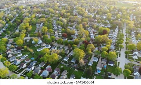 Aerial view of residential houses at spring (may). American neighborhood, suburb.  Real estate, drone shots, sunset, sunlight, from above.