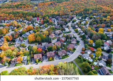 Aerial view of residential neighborhood showing trees changing color during fall season in Montreal, Quebec, Canada.