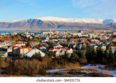 Aerial view of Reykjavik, Iceland with snow capped mountains in the background