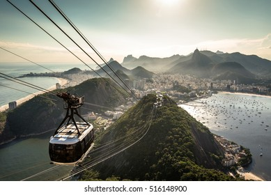 Aerial View of Rio de Janeiro from the Sugarloaf Mountain by Sunset and a Cable Car Approaching