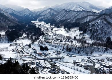 Aerial view from Risshaku-ji Buddhist Temple on mountainside overlooking Yamadera village in the valley & a train of JR Senzan Railway traveling on a bridge in snowy winter season in Yamagata, Japan