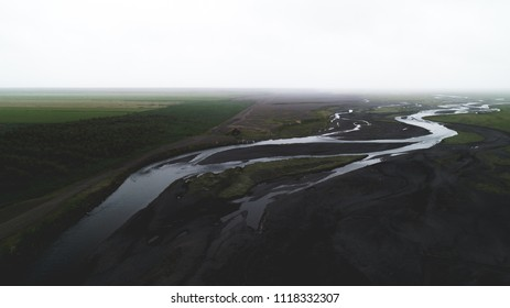 aerial view of river in black sand with many junctions drone
