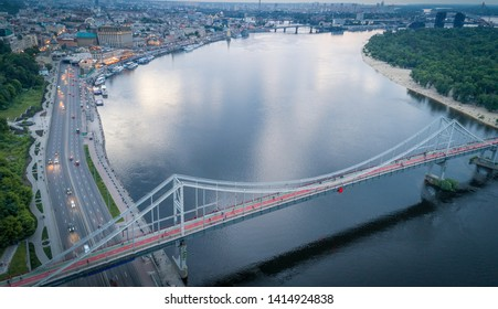 Aerial view of the river Dnieper, Kiev hills and the city of Kiev near the pedestrian bridge, Ukraine. Night city, twilight, backlight