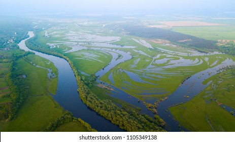 Aerial view of river flood. Beautiful flooded meadow. Flying above beautiful Desna river when the river is full of water at spring at National Nature Park in Chernihiv Oblast, Ukraine.
