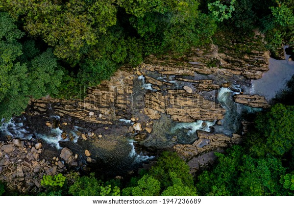 Aerial view of river going through a rock bed that is worn out from the water