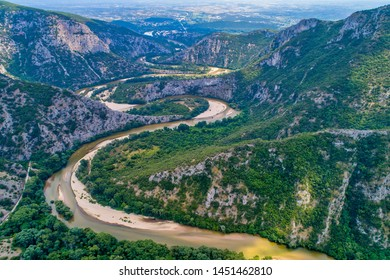 Aerial view of the river Nestos in Xanthi, Greece. The Nestos River forms on its long journey landscapes of unique beauty with rich forests, rare wetlands. favorite destination for canoe and kayak - Shutterstock ID 1451462810