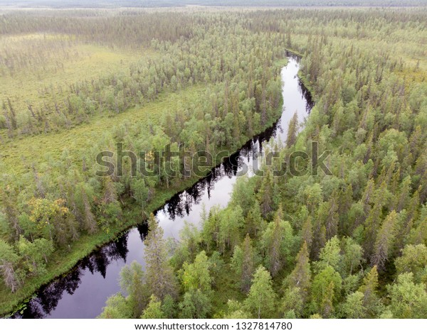 Aerial view of river and nordic forest in Lappish landscape, Finland