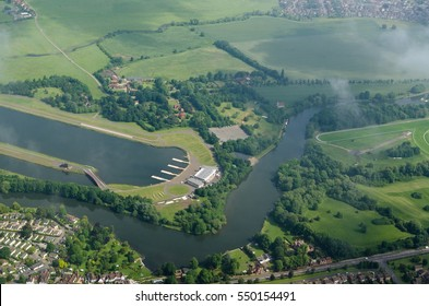 Aerial view of the River Thames between Eton and Windsor with the renowned rowing venue Eton Dorney Lake to the left and part of Windsor Racecourse to the right.  Slightly cloudy summer morning.