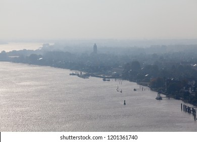 aerial view of the river Weser at Brake (Unterweser), Germany with silhouette of the historic watertower in the quater Kirchhammelwarden on a sunny but misty day
