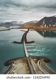 Aerial view of road 1 in iceland with bridge over the sea in Snaefellsnes peninsula with clouds, water and mountain in background