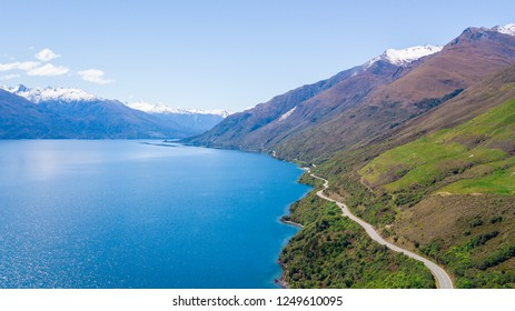 Aerial view of Road along the Lake Wanaka with snow capped mountain behind the lake in the sunny blue sky day, Wanaka, New Zealand