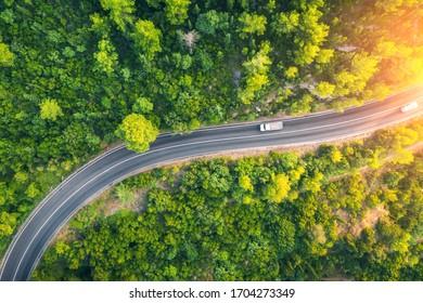 Luftbild der Straße in schönen grünen Wald bei Sonnenuntergang im Frühling. Farbige Landschaft mit Auto auf der Straße, Bäume im Sommer. Draufsicht von der Autobahn in Kroatien.Von oben anzeigen. Reisen