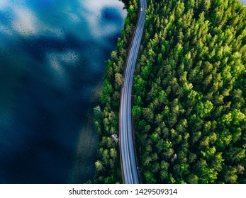 Aerial view of road between green summer forest and blue lake in Finland
