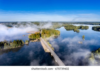 Aerial view of a road between lakes in morning mist in Finland
