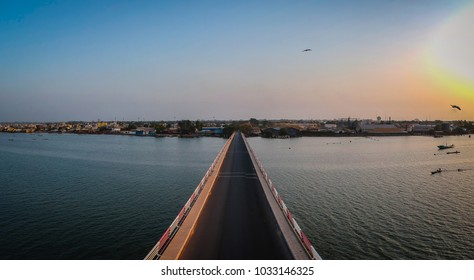 Aerial view of the road bridge over casamance river in Ziguinchor, Senegal, Africa during a sunset. Drone picture looking towards the city above the driving platform.