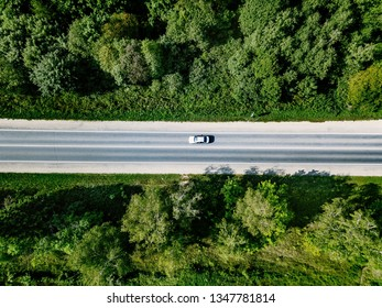 Aerial view of road with car going through green spring forest.