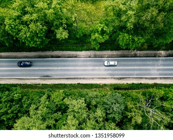 Aerial view of road with cars going through green spring forest.