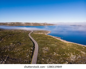 Aerial view. Road crossing Hardangervidda mountain plateau, clouds over lakes, morning time. Norway landscape. National tourist Hardangervidda route.