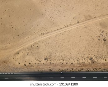 Aerial view of a road in the desert, cyclist racing on the bicycle on the black asphalt. Outdoor sports, cycling, tourism. Lanzarote, Canary Islands, Spain. Africa