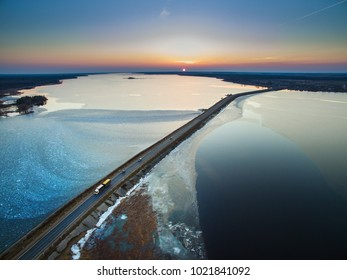 Aerial view of road in the frozen lake with moving cars on sunset, early spring top view.