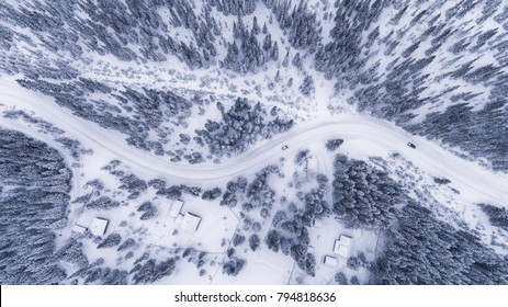 Aerial view of a road in idyllic winter landscape. Winter traffic conditions