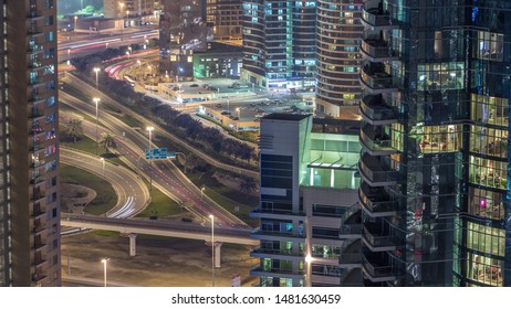 Aerial view of a road intersection in a big city night timelapse. Urban landscape of Dubai Marina and JLT district in UAE with cars and metro