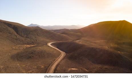 Vista aérea de una carretera que atraviesa una amplia zona de tierras y montañas volcánicas