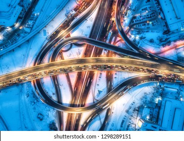 Aerial view of road in the modern city at night in winter. Top view of traffic in highway with city illumination. Cars on elevated road and interchange overpass. Busy intersection. Expressway at dusk