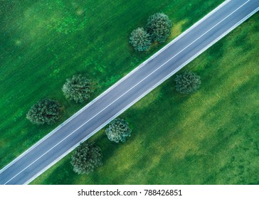Aerial view of road through beautiful green field in the evening in spring. Beautiful landscape with empty rural road, trees, green grass. Highway through the park. Top view from flying drone. Nature