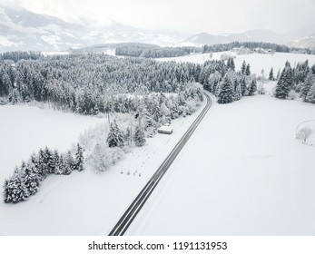 Aerial view of road through winter alpine forest