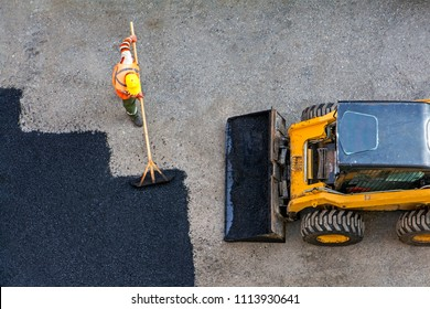Aerial view of road worker repair asphalt covering and yellow asphalting paver machine. Contrast between new and old road surface