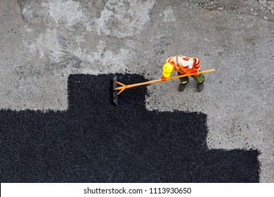 Aerial view of road worker repair asphalt covering. Contrast between new and old road surface