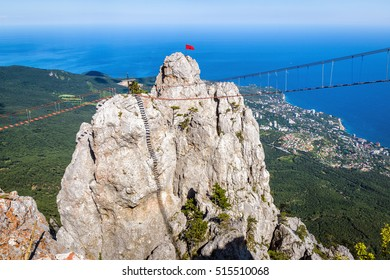 Aerial view of rock with a rope bridge on the Mount Ai-Petri in Crimea, Russia. Ai-Petri is one of the highest mountains in Crimea and tourist attraction. Hanging bridge on Ai-Petri over the abyss.