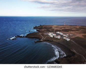 Aerial view of rocky coastline with white buildings and a lighthouse on Tenerife, Canary Islands, Spain. Wild Coast of the Atlantic Ocean