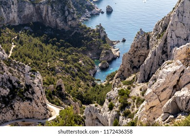 aerial view of rocky mountains, winding road and calm sea harbour in Calanques de Marseille (Massif des Calanques), provence, france