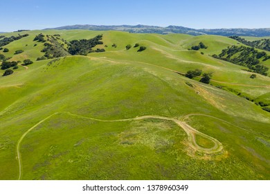 An aerial view of rolling hills in Northern California's tri-valley region shows lush, green grass that flourished after a wet winter. This beautiful area generally has a very hot, dry climate.