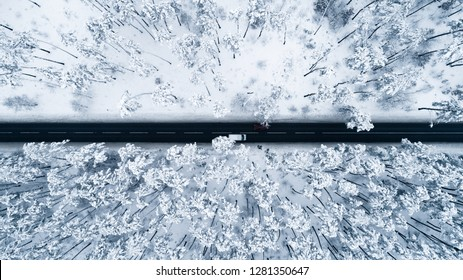 Aerial view of the romantic road passing through the snow-covered winter forest. A view down to the tops of the pines and a black strip of asphalt road in the middle.