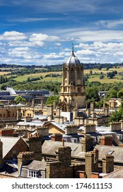 Aerial view of roofs and spires of oxford with green English countryside and blue sky in background