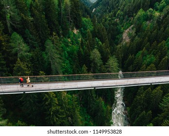 Aerial view of rope walkway through treetops in coniferous forest. Bird's eye view of hanging bridge crossing raging mountains river, suspension bridge with walking people traveller