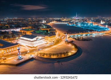 Aerial view of Rostral Columns in Vasilievskiy Island, night lights, river Neva frome drone