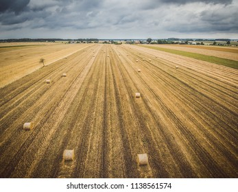 Aerial view of round hay bales on stubble with a village in the background