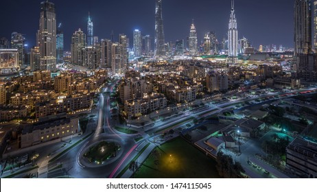 Aerial view of a roundabout circle road in Dubai downtown with old style traditional buildings from above night timelapse. Traffic on the street. Dubai, United Arab Emirates.