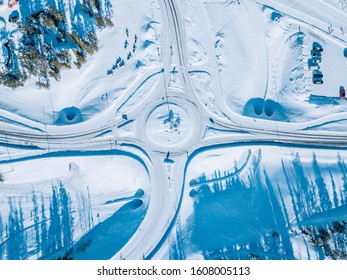 Aerial view of roundabout road intersection with snow winter road with a circular motion in Finland.
