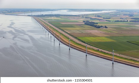 Aerial view row offshore wind turbines along coast and dike of Flevoland, The Netherlands
