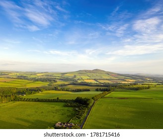Aerial view of Ruberslaw in the Scottish Borders, on a summer morning just after sunrise. Nearby towns and villages, Bonchester, Hawick and Jedburgh.