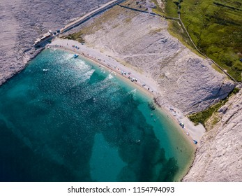 Aerial view of Rucica beach on Pag island, Metajna, Croatia. Transparent seabed wild and desert nature, bathers, relaxation and summer holidays. Promontories and cliffs of Croatian coasts.